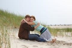 Pares felizes novos no amor que tem o divertimento em dunas de areia da praia Fotografia de Stock