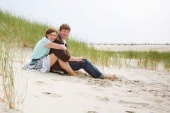 Pares felizes novos no amor que tem o divertimento em dunas de areia da praia Imagens de Stock Royalty Free