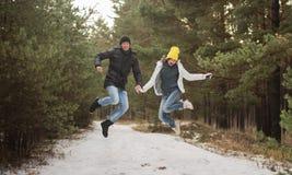 Pares felizes novos no salto do parque do inverno Família ao ar livre Amor Imagem de Stock