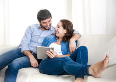 Pares felizes novos no sofá em casa que aprecia usando o tablet pc digital fotos de stock