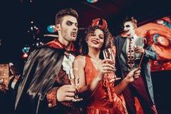 Pares felizes novos nos trajes no partido de Dia das Bruxas foto de stock
