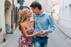 Pares felizes novos que abraçam ao andar na rua fotografia de stock