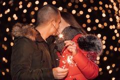 Pares felizes novos que abraçam e que beijam na noite da cidade do inverno fotos de stock