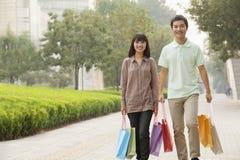 Pares felizes novos que andam com os sacos de compras coloridos nas mãos no Pequim, China Foto de Stock Royalty Free