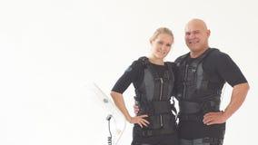 Pares felizes novos que apreciam a formação com ternos do EMS video estoque