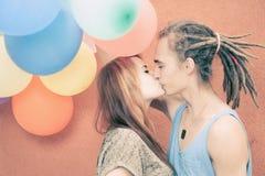 Pares felizes novos que beijam e que guardam balões Imagens de Stock Royalty Free