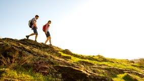 Pares felizes novos que caminham com as trouxas em Rocky Trail bonito em Sunny Evening Curso e aventura da família