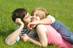 Pares felizes novos que colocam em uma grama verde Fotografia de Stock Royalty Free