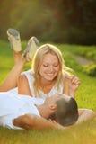 Pares felizes novos que encontram-se para baixo na grama no sol Foto de Stock
