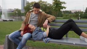 Pares felizes novos que guardam as mãos e que descansam junto no banco no parque da cidade filme