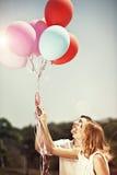 Pares felizes novos que guardam ballons e o sorriso coloridos Imagens de Stock Royalty Free