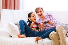 Pares felizes novos que jogam o console Fotografia de Stock