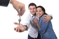 Pares felizes novos que recebem a residência nova chave da casa no conceito de estado real Foto de Stock