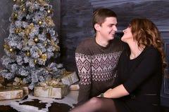 Pares felizes novos que sentam-se na frente da árvore de Natal Fotos de Stock Royalty Free