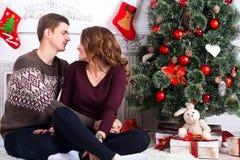 Pares felizes novos que sentam-se na frente da árvore de Natal Foto de Stock Royalty Free