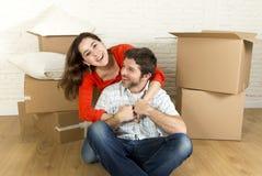 Pares felizes novos que sentam-se no assoalho que comemora junto mover-se na casa ou no apartamento liso novo foto de stock
