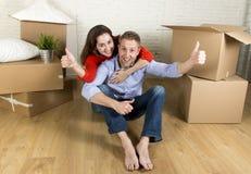 Pares felizes novos que sentam-se no assoalho que comemora junto mover-se na casa ou no apartamento liso novo fotografia de stock