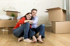 Pares felizes novos que sentam-se no assoalho que comemora junto mover-se na casa ou no apartamento liso novo imagens de stock