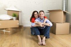 Pares felizes novos que sentam-se no assoalho que comemora junto mover-se na casa ou no apartamento liso novo fotografia de stock royalty free