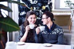 Pares felizes novos que sorriem entre si e que guardam copos Árvore de Natal fotografia de stock royalty free