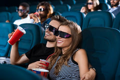 Pares felizes novos que têm uma data no cinema Foto de Stock