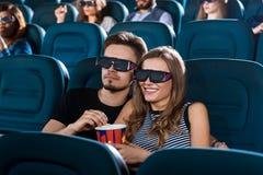 Pares felizes novos que têm uma data no cinema Foto de Stock Royalty Free