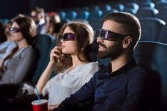 Pares felizes novos que têm uma data no cinema Imagens de Stock