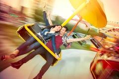 Pares felizes novos que têm o divertimento no parque de diversões Fotografia de Stock