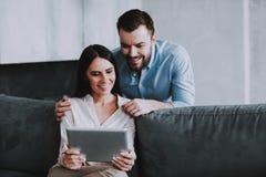 Pares felizes novos usando o dispositivo da tabuleta em casa imagens de stock royalty free