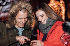 Pares felizes novos usando o smartphone na noite fotografia de stock royalty free
