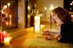 Pares felizes por uma chaminé no Natal Fotografia de Stock Royalty Free