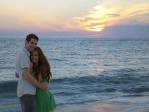 Pares felizes que abraçam durante a praia do por do sol fotografia de stock
