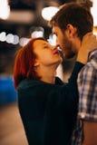 Pares felizes que abraçam e que beijam na noite no festões leves imagem de stock
