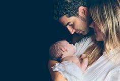 Pares felizes que abraçam e que olham recém-nascidos sobre Foto de Stock Royalty Free