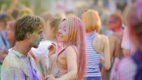Pares felizes que abraçam, flertando e dançando na multidão no festival exterior da cor video estoque
