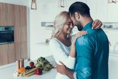 Pares felizes que abraçam na cozinha Relacionamento romântico fotos de stock