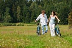 Pares felizes que andam com bicicletas antiquados Fotografia de Stock Royalty Free