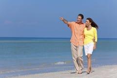 Pares felizes que andam e que apontam em uma praia Foto de Stock