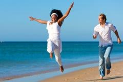 Pares felizes que andam e que funcionam na praia foto de stock royalty free