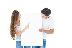 Pares felizes que apontam um cartaz branco fotos de stock royalty free