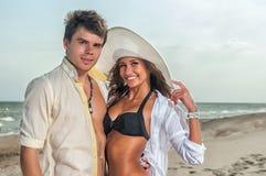 Pares felizes que apreciam férias na praia Imagens de Stock