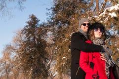 Pares felizes que apreciam no dia de inverno ensolarado bonito Fotografia de Stock Royalty Free