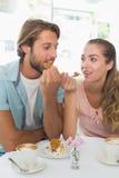 Pares felizes que apreciam o café e o bolo Foto de Stock Royalty Free