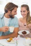 Pares felizes que apreciam o café e o bolo Fotografia de Stock Royalty Free