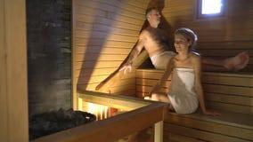Pares felizes que apreciam a sauna junto video estoque