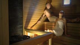 Pares felizes que apreciam a sauna junto vídeos de arquivo