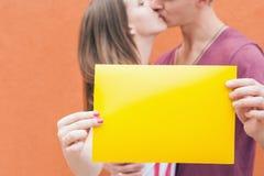 Pares felizes que beijam e que guardam o quadro no fundo vermelho Imagem de Stock