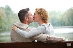 Pares felizes que beijam no banco de parque fotografia de stock