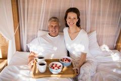 Pares felizes que comem o café da manhã na cama do dossel imagem de stock royalty free