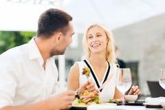 Pares felizes que comem o jantar no terraço do restaurante foto de stock